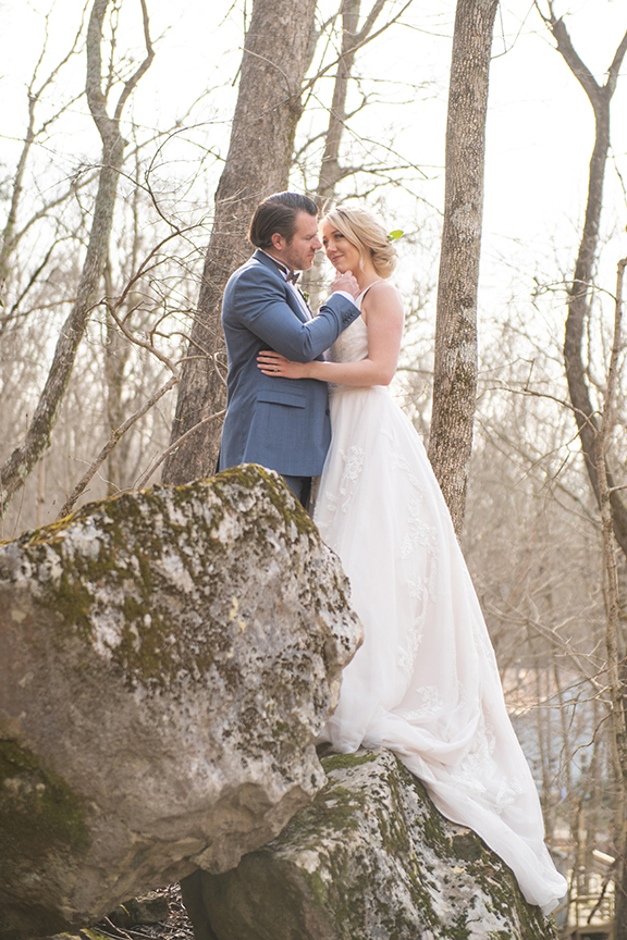 Beautiful wedding couple in the forest, standing among mossy rocks in early spring