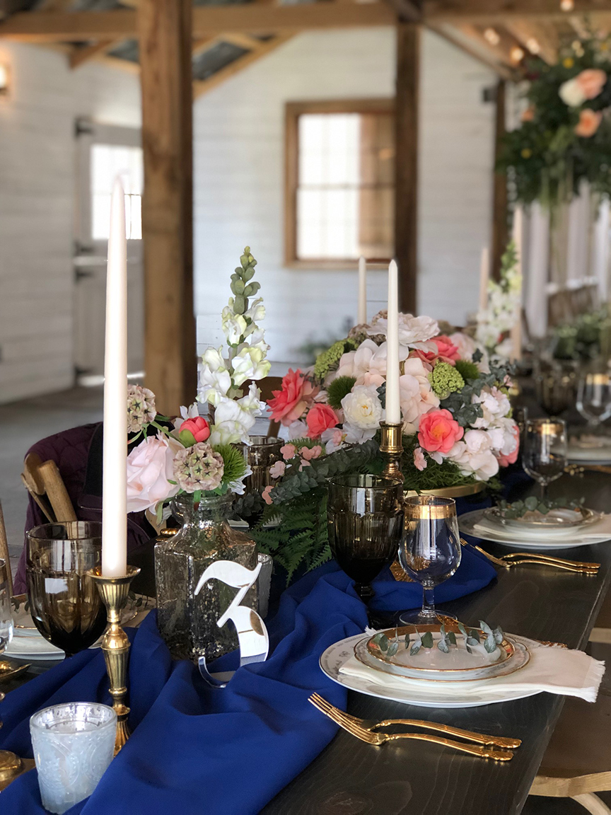 navy blue and coral wedding table setting, white candles, white barn