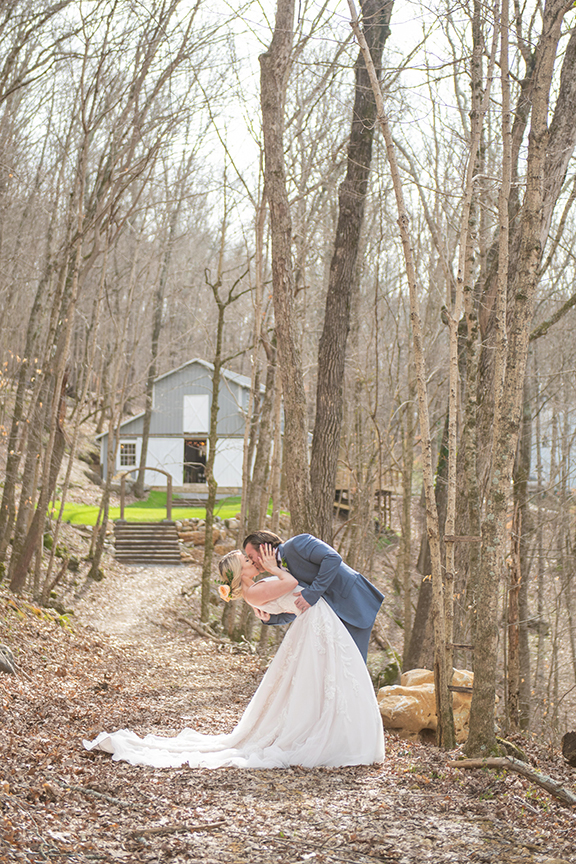 Bride and groom deep dip in photo in forest, barn in background