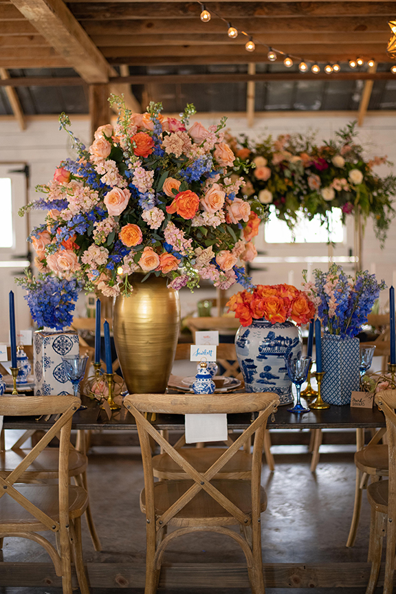 a blue and white table setting with blue willow china, a massive oversize gold vase overflowing with flowers, and many more blue and white vases with blue candles